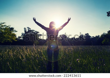 Young girl spreading hands with joy and inspiration facing the sun,sun greeting,freedom ,freedom concept,meditation zen  - stock photo