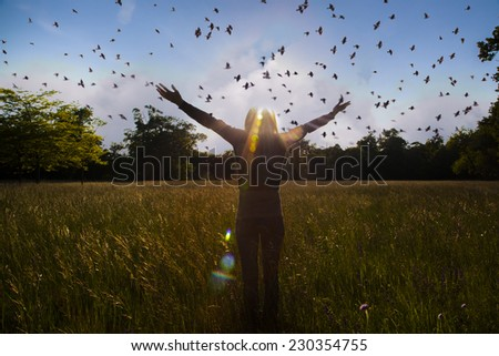 Young girl spreading hands with joy and inspiration facing the sun,sun greeting,freedom ,freedom concept,bird flying above - stock photo