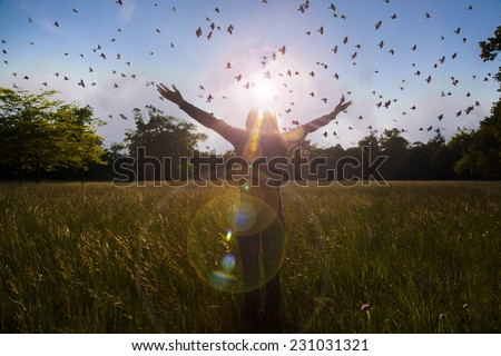 Young girl spreading hands with joy and inspiration facing the sun,sun greeting,freedom ,freedom concept,bird flying above,imaginary landscape - stock photo