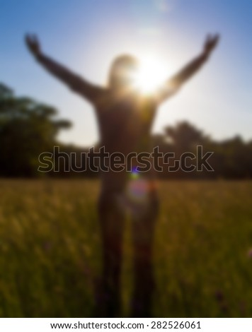 Young girl spreading hands with joy and inspiration facing the sun,sun greeting,freedom ,freedom concept,imaginary landscape - stock photo