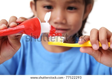 Young girl squeezing tooth paste on a toothbrush