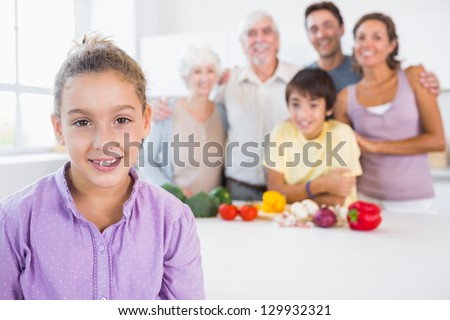 Young girl standing beside kitchen counter with family behind her - stock photo
