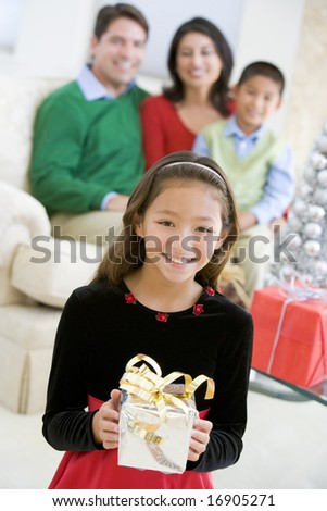 Young Girl Standing Holding Christmas Present,With Her Parents And Brother Sitting In The Background