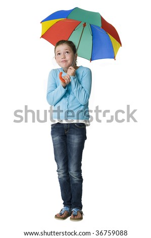 Young girl standing huddled under colorful umbrella - stock photo