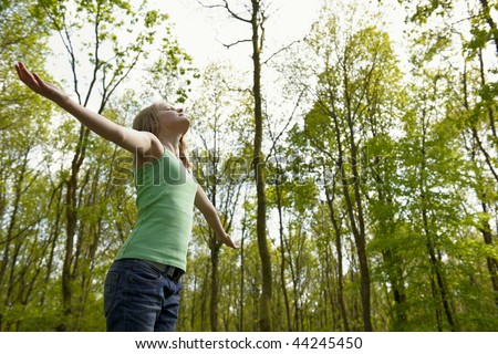 young girl standing in a forest enjoying the fresh air - stock photo