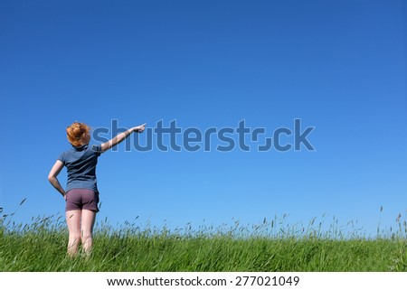 Young girl standing in meadow pointing to sky - stock photo