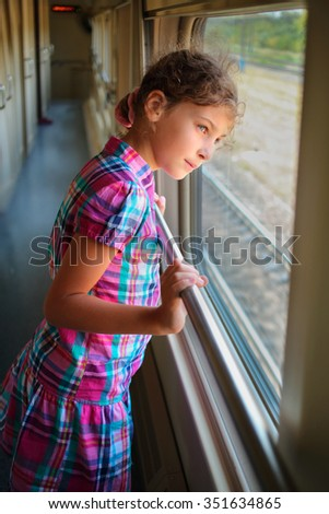 Young girl standing inside train and looking trough window - stock photo