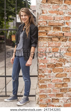Young girl standing on a street near the brick wall. - stock photo