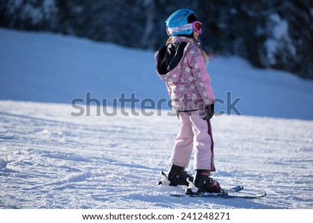 Young girl standing on skis on the slopes on a sunny morning in snowy mountain.Child at a ski resort in the mountains.Ski school.Winter vacation - stock photo