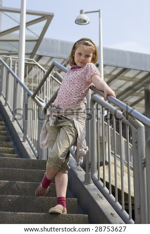 Young girl standing on steps - stock photo