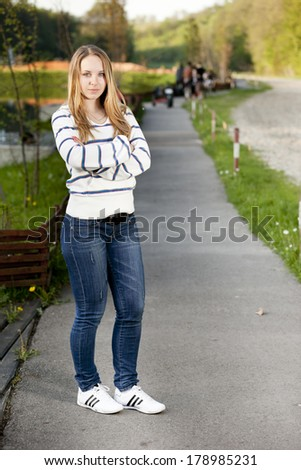 Young girl standing outdoors against the backdrop of the lake