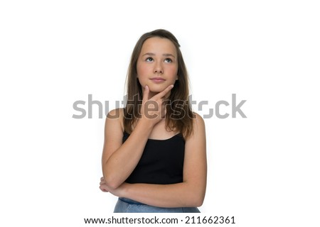 Young girl standing thinking with her hand to her chin looking up into the air with a contemplative expression, isolated on white - stock photo