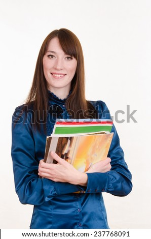 Young girl standing with a stack of magazines - stock photo
