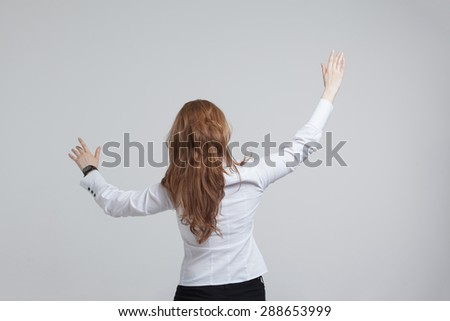 Young girl stands back and working with virtual screen on gray background - stock photo