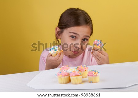 Young girl staring at two cupcakes with a smirk trying to decide which to eat first - stock photo