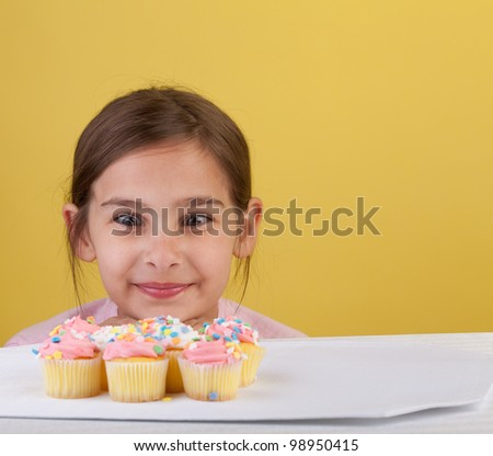 Young girl staring cross eyed at a bunch of cupcakes  on a yellow background - stock photo