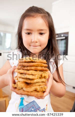 Young girl staring intently at stack of large homemade cookies - stock photo