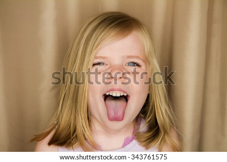 Young girl sticking her tongue out making a funny face - stock photo