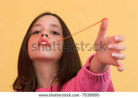 Young girl stretching a chewing gum from her mouth - stock photo