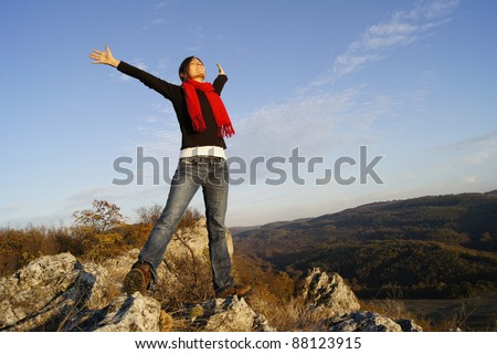 Young girl stretching her arms on top of a mountain feeling success - stock photo