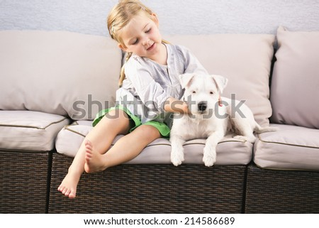 Young girl stroking her dog on couch sitting - stock photo