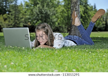 Young girl student on the grass with laptop.