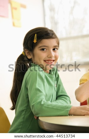 Young girl student sitting in school classroom. Vertically framed shot. - stock photo