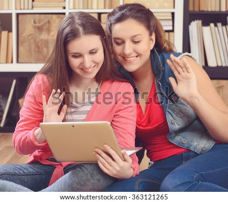 Young girl student sitting in the library and use of a laptop - stock photo