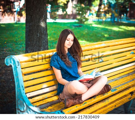 Young girl student sitting on yellow bench with book - stock photo