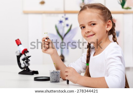 Young girl study plants in biology class - holding a seedling and test tube - stock photo