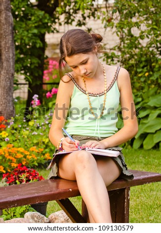 Young girl studying in garden, outdoors - stock photo