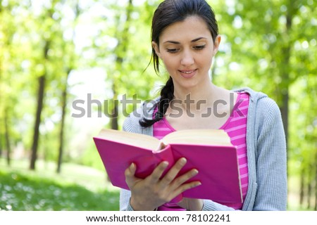young girl studying in nature, smiling and  holding  book