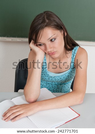 Young girl studying in school, looking bored - stock photo