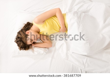 young girl  suffering from stomach ache lying on bed at home