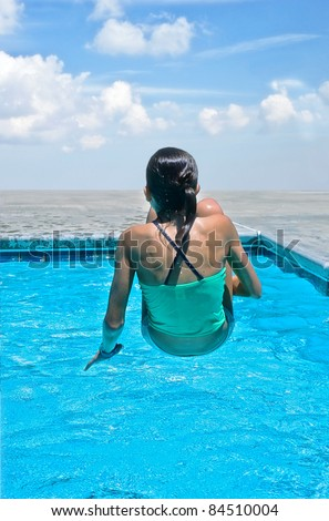 Young girl suspended over the water in a swimming pool. - stock photo