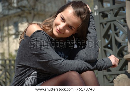 Young girl, sweet female model. Teenager sitting on the stairs, holding her hairs, happy face expression.
