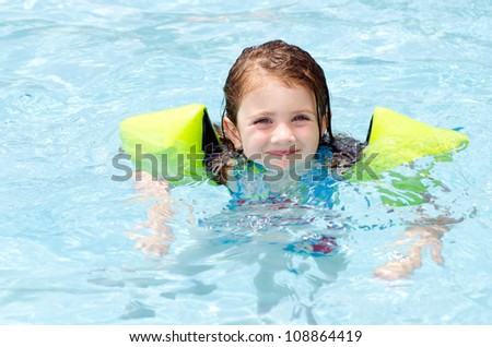 Young girl swimming in pool during hot day in summer - stock photo