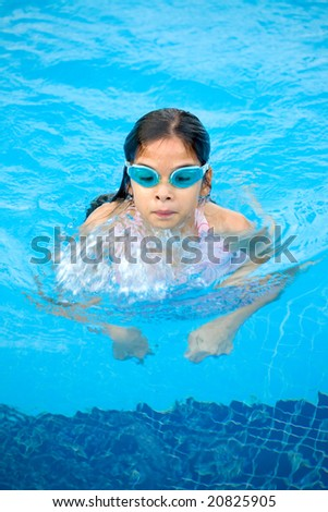 Young girl swimming in the pool - stock photo