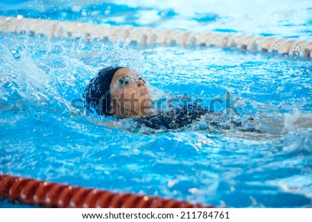 Young girl swimming on her back in the pool - stock photo