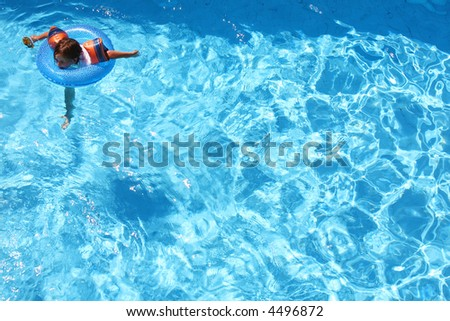 Young girl swimming with arm bands and a ring in a pool all on her own