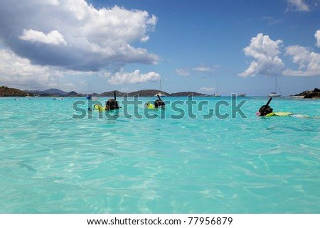 Young girl swims to her Dad and brother, snorkeling in St. John - stock photo