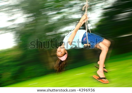 Young girl swinging fast while lying down backwards on a rope swing attached to a tree. - stock photo