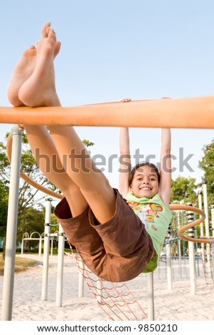 Young girl swinging on a bar in the playground - stock photo