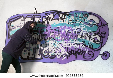 Young girl tagging wall with graffiti, enjoyment - stock photo