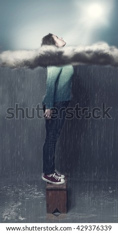 Young girl take out her head through clouds on a rainy weather - stock photo
