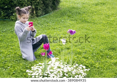 Young girl takes a picture with a phone of spring flowers - stock photo