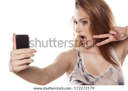 young girl takes a self portrait with her smart phone - stock photo