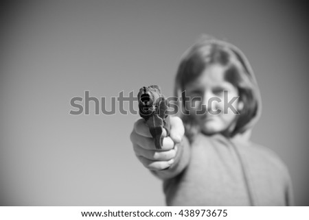 young girl taking aim and pointing a gun