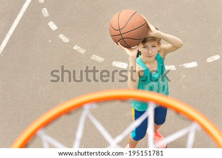 Young girl taking aim at the goal on a basketball court standing with the ball raised aiming at the hoop, view from above - stock photo