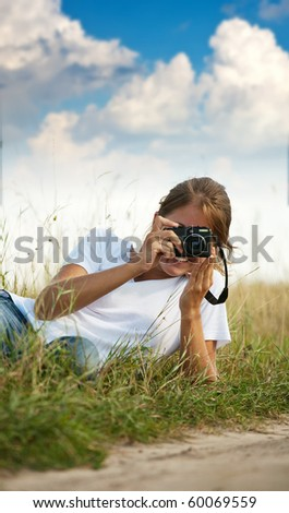Young girl taking photo with camera against blue sky - stock photo